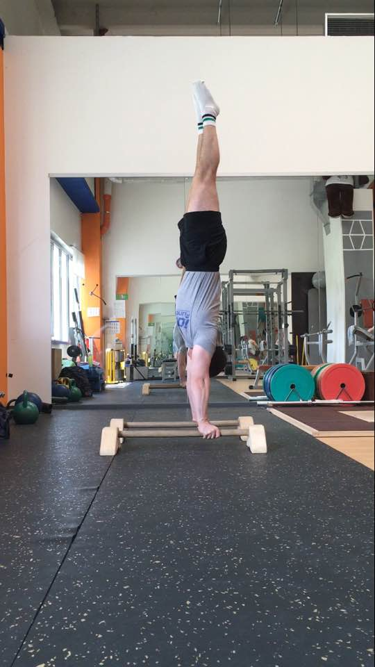 Alessandro Mainente esegue la verticale alle parallele